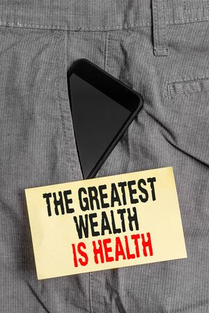 Word writing text The Greatest Wealth Is Health. Business photo showcasing Many sacrifice their money just to be healthy Smartphone device inside formal work trousers front pocket near note paper Stock fotó