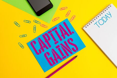 Word writing text Capital Gains. Business photo showcasing Bonds Shares Stocks Profit Income Tax Investment Funds Blank spiral notepad pencil clips smartphone paper sheets color background