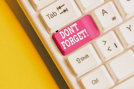 Conceptual hand writing showing Don T Forget. Concept meaning used to remind someone about an important fact or detail White pc keyboard with note paper above the white background