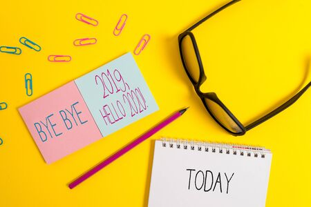 Text sign showing Bye Bye 2019 Hello 2020. Business photo showcasing saying goodbye to last year and welcoming another good one Square blank sticky notepads pencil clips eyeglasses yolk color background