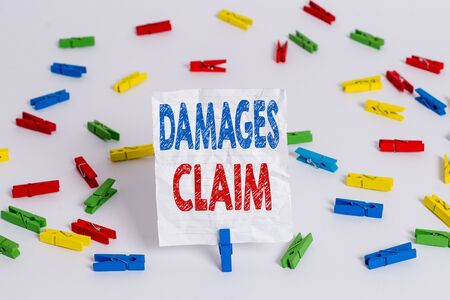 Text sign showing Damages Claim. Business photo showcasing Deanalysisd Compensation Litigate Insurance File Suit Colored clothespin papers empty reminder white floor background office