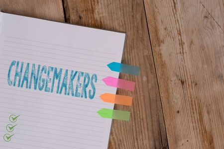 Handwriting text writing Changemakers. Conceptual photo Young Turk Influencers Acitivists Urbanization Fashion Gen X Striped note book four colored arrow banners reminder wooden background Stock Photo