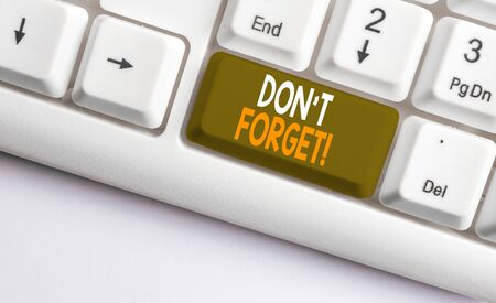Text sign showing Don T Forget. Business photo showcasing used to remind someone about an important fact or detail White pc keyboard with empty note paper above white background key copy space