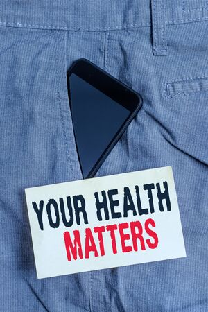 Word writing text Your Health Matters. Business photo showcasing good health is most important among other things Smartphone device inside formal work trousers front pocket near note paper