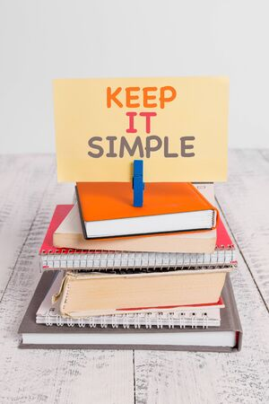 Conceptual hand writing showing Keep It Simple. Concept meaning to make something easy to understand and not in fancy way pile stacked books notebook pin color reminder white wooden
