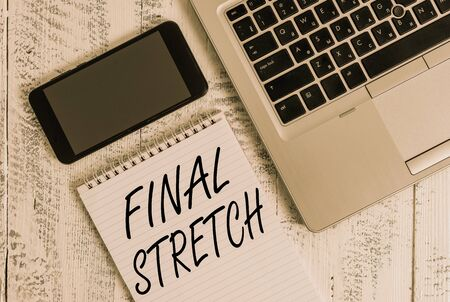 Handwriting text Final Stretch. Conceptual photo Last Leg Concluding Round Ultimate Stage Finale Year ender Metallic laptop blank ruled notepad smartphone lying old wooden table Imagens