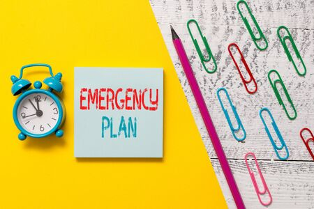 Handwriting text Emergency Plan. Conceptual photo procedures for handling sudden or unexpected situations Notepad marker pen colored paper sheet clips alarm clock wooden background
