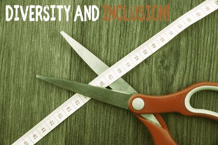 Word writing text Diversity And Inclusion. Business photo showcasing range huanalysis difference includes race ethnicity gender Front view wooden background scissors cutting through tape measuring diet