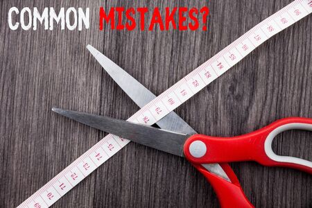 Word writing text Common Mistakes Question. Business photo showcasing repeat act or judgement misguided making something wrong Front view wooden background scissors cutting through tape measuring diet