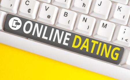 Conceptual hand writing showing Online Dating. Concept meaning Searching Matching Relationships eDating Video Chatting White pc keyboard with note paper above the white background Фото со стока