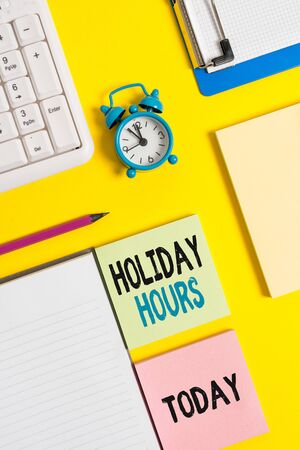 Conceptual hand writing showing Holiday Hours. Concept meaning employee receives twice their normal pay for all hours Crumpled white paper on table clock mobile and pc keyboard