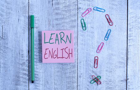 Word writing text Learn English. Business photo showcasing Universal Language Easy Communication and Understand Pastel colour note paper placed next to stationary above the wooden table