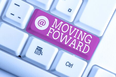 Writing note showing Moving Foward. Business concept for Towards a Point Move on Going Ahead Further Advance Progress White pc keyboard with note paper above the white background Stockfoto