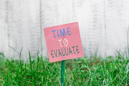 Writing note showing Time To Evaluate. Business concept for judge something with respect to its worth or significance Plain paper attached to stick and placed in the grassy land