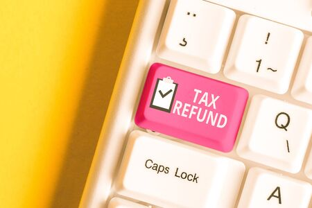 Handwriting text writing Tax Refund. Conceptual photo refund on tax when the tax liability is less than the tax paid White pc keyboard with empty note paper above white background key copy space Stock Photo