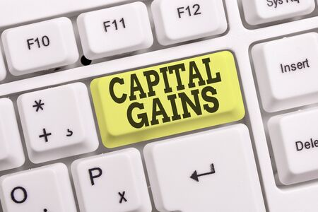 Conceptual hand writing showing Capital Gains. Concept meaning Bonds Shares Stocks Profit Income Tax Investment Funds White pc keyboard with note paper above the white background Stock Photo