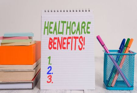Text sign showing Healthcare Benefits. Business photo text monthly fair market valueprovided to Employee dependents Pens metal holder stacked note pads books square box spiral wooden table 写真素材