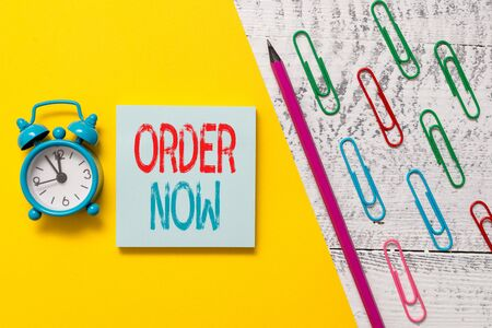 Handwriting text Order Now. Conceptual photo the activity of asking for goods or services from a company Notepad marker pen colored paper sheet clips alarm clock wooden background Stock Photo