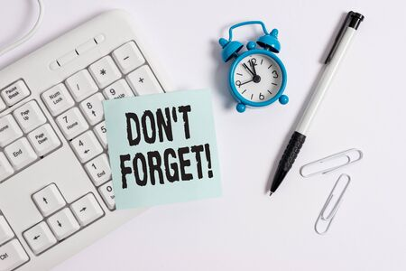 Conceptual hand writing showing Don T Forget. Concept meaning used to remind someone about an important fact or detail White pc keyboard with empty note paper above white background