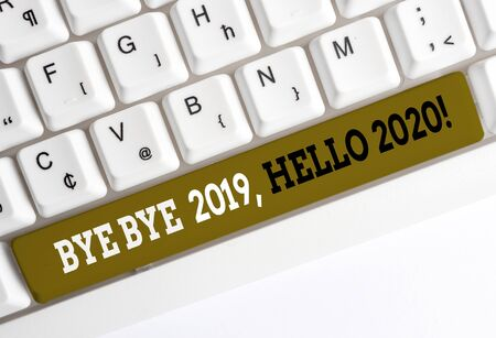Handwriting text writing Bye Bye 2019 Hello 2020. Conceptual photo saying goodbye to last year and welcoming another good one White pc keyboard with empty note paper above white background key copy space Imagens