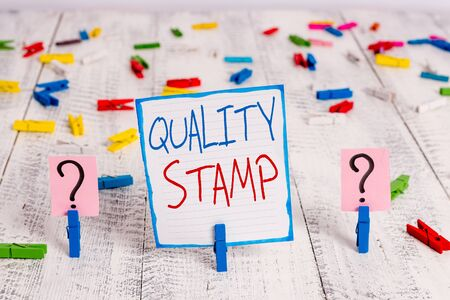Conceptual hand writing showing Quality Stamp. Concept meaning Seal of Approval Good Impression Qualified Passed Inspection Crumbling sheet with paper clips placed on the wooden table