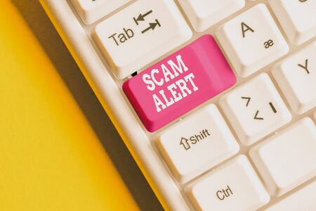 Conceptual hand writing showing Scam Alert. Concept meaning unsolicited email that claims the prospect of a bargain White pc keyboard with note paper above the white background