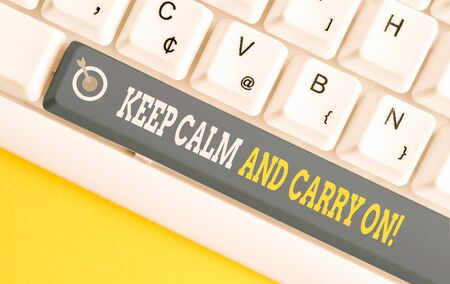 Handwriting text writing Keep Calm And Carry On. Conceptual photo slogan calling for persistence face of challenge White pc keyboard with empty note paper above white background key copy space