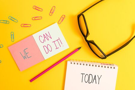 Text sign showing We Can Do It. Business photo showcasing see yourself as powerful capable demonstrating Square blank sticky notepads pencil clips eyeglasses yolk color background