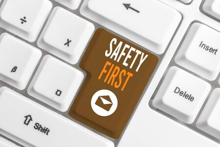 Conceptual hand writing showing Safety First. Concept meaning used to say that the most important thing is to be safe White pc keyboard with note paper above the white background Stock Photo - 129852942