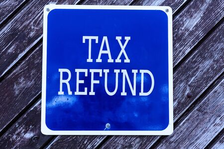 Handwriting text writing Tax Refund. Conceptual photo refund on tax when the tax liability is less than the tax paid Empty blue board with copy space above wooden background Stock Photo