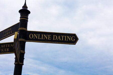 Text sign showing Online Dating. Business photo text Searching Matching Relationships eDating Video Chatting Road sign on the crossroads with blue cloudy sky in the background Фото со стока - 129852801