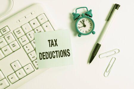 Conceptual hand writing showing Tax Deductions. Concept meaning an amount or cost that subtracted from someone s is income White pc keyboard with empty note paper above white background