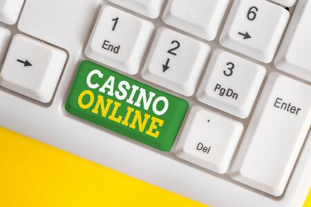 Handwriting text Casino Online. Conceptual photo Computer Poker Game Gamble Royal Bet Lotto High Stakes White pc keyboard with empty note paper above white background key copy space