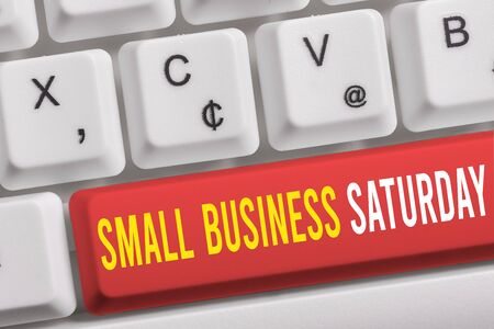 Word writing text Small Business Saturday. Business photo showcasing American shopping holiday held during the Saturday White pc keyboard with empty note paper above white background key copy space 写真素材