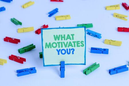 Conceptual hand writing showing What Motivates Youquestion. Concept meaning know reasons why you want to wake up each morning Colored clothespin papers empty reminder white floor office