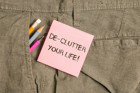 Conceptual hand writing showing De Clutter Your Life. Concept meaning remove unnecessary items from untidy or overcrowded places Writing equipment and pink note paper inside pocket of trousers