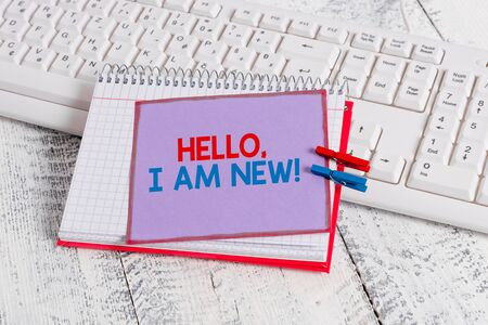 Word writing text Hello I Am New. Business photo showcasing introducing oneself in a group as fresh worker or student notebook paper reminder clothespin pinned sheet white keyboard light wooden
