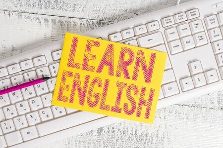 Text sign showing Learn English. Business photo showcasing Universal Language Easy Communication and Understand White keyboard office supplies empty rectangle shaped paper reminder wood 写真素材