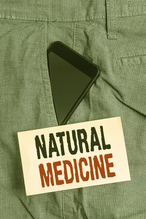 Word writing text Natural Medicine. Business photo showcasing any of various systems of healing or treating disease Smartphone device inside formal work trousers front pocket near note paper Фото со стока