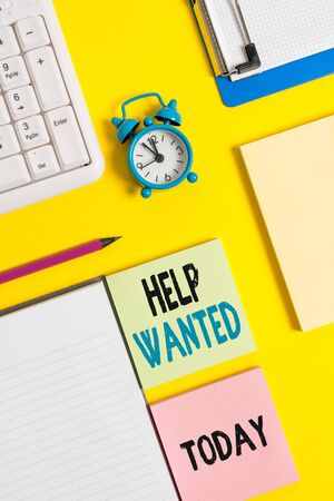 Conceptual hand writing showing Help Wanted. Concept meaning An ad in the paper an employer places to find a new employee Crumpled white paper on table clock mobile and pc keyboard
