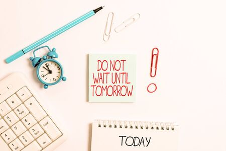 Writing note showing Do Not Wait Until Tomorrow. Business concept for needed to do it right away Urgent Better do now Copy space on empty note paper with clock and pencil on the table