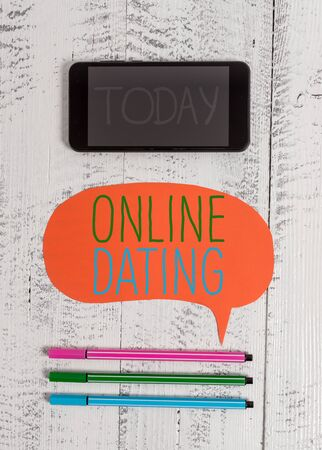 Writing note showing Online Dating. Business concept for Searching Matching Relationships eDating Video Chatting Smartphone cell pens blank colored speech bubble wooden background Фото со стока - 129852358