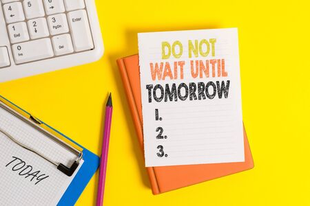Writing note showing Do Not Wait Until Tomorrow. Business concept for needed to do it right away Urgent Better do now Pile of empty papers with copy space on the table Foto de archivo