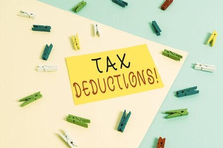 Text sign showing Tax Deductions. Business photo text reduction income that is able to be taxed of expenses Colored clothespin paper empty reminder yellow blue floor background office Stock Photo