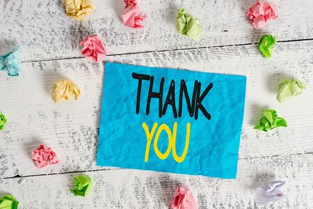 Word writing text Thank You. Business photo showcasing a polite expression used when acknowledging a gift or service Crumpled colored rectangle square shaped paper reminder white wood desk