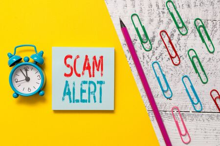 Handwriting text Scam Alert. Conceptual photo unsolicited email that claims the prospect of a bargain Notepad marker pen colored paper sheet clips alarm clock wooden background Stock Photo - 129852172