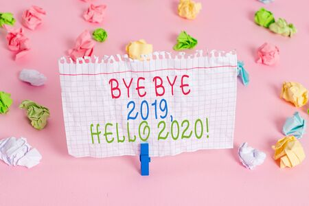 Conceptual hand writing showing Bye Bye 2019 Hello 2020. Concept meaning saying goodbye to last year and welcoming another good one Colored crumpled papers empty reminder pink floor clothespin