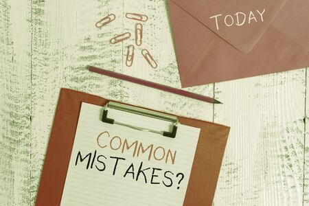 Conceptual hand writing showing Common Mistakes Question. Concept meaning repeat act or judgement misguided making something wrong Colored clipboard paper sheet pencil clips wooden background