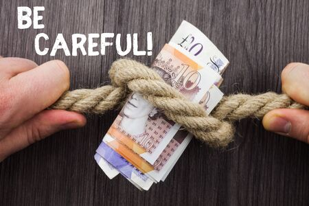 Writing note showing Be Careful. Business concept for making sure of avoiding potential danger mishap or harm Front view wooden background two hands knot rope bills inside symbol