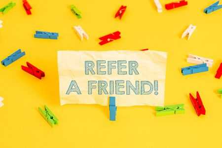 Writing note showing Refer A Friend. Business concept for direct someone to another or send him something like gift Colored clothespin papers empty reminder yellow floor background office